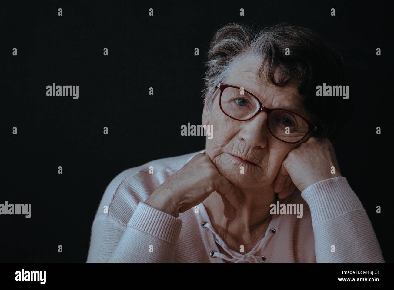 Sad, old woman wearing eyeglasses, black background - Stock Image