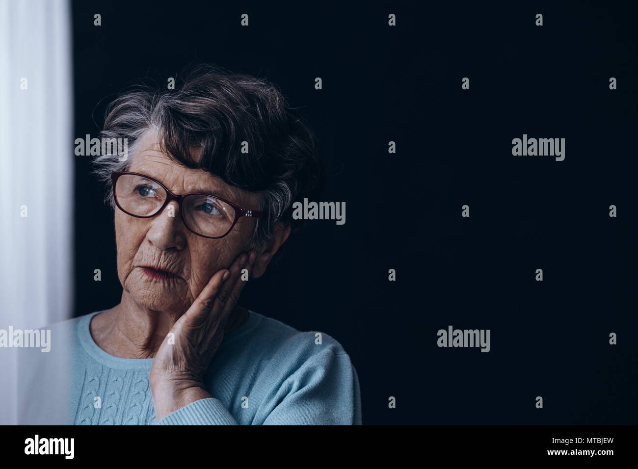 Sad, old woman standing alone in dark room - Stock Image