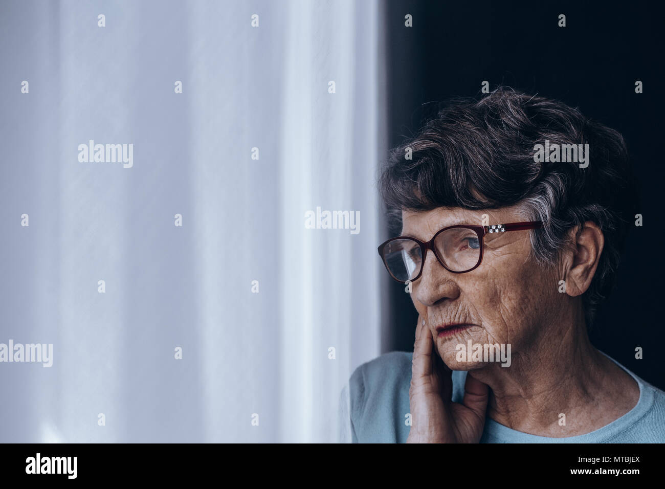 Sad, lonely senior woman suffering from depression - Stock Image