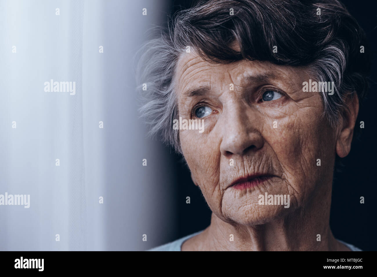 Portrait of despair, old woman standing beside window - Stock Image