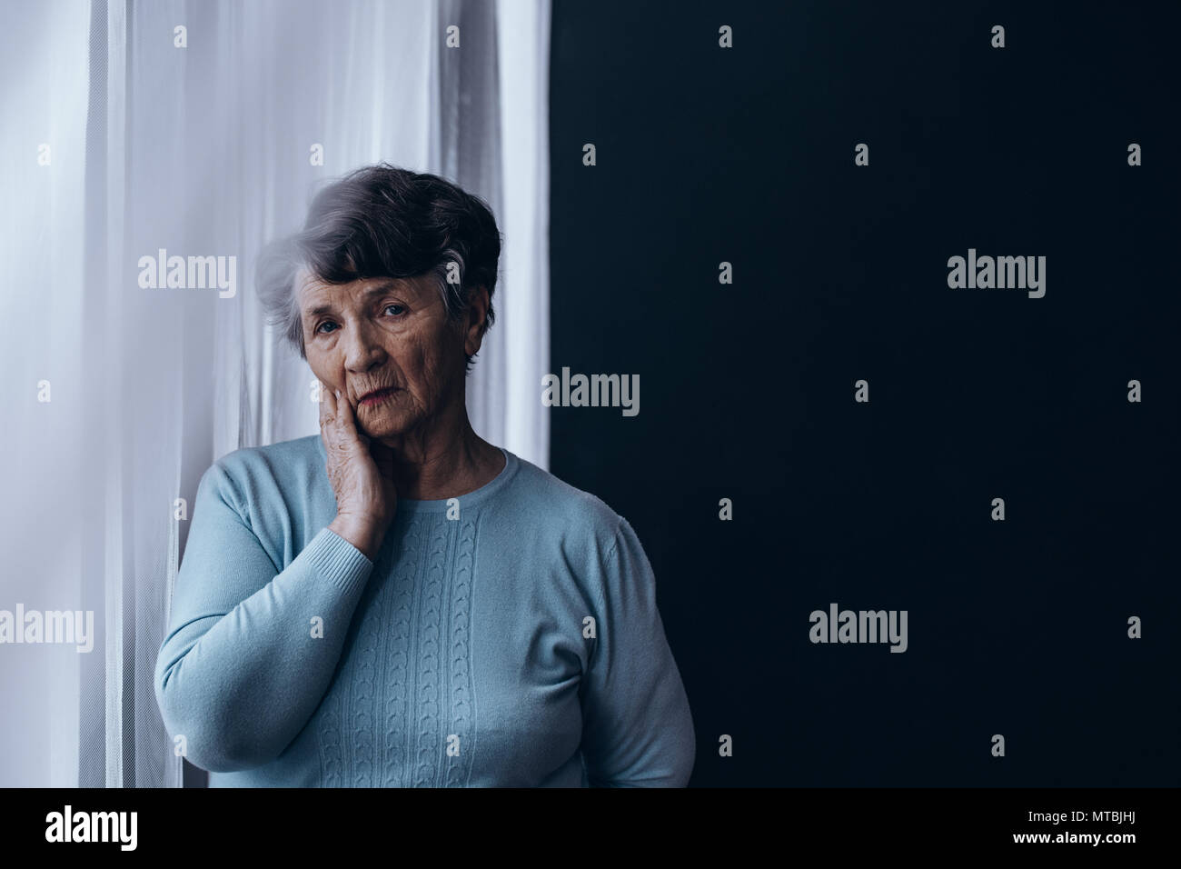 Sad, elderly woman standing alone beside window - Stock Image