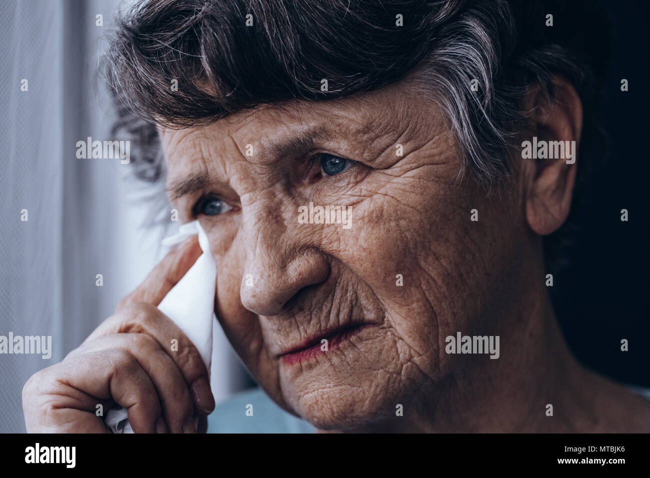 Portrait of crying senior woman, holding tissue - Stock Image