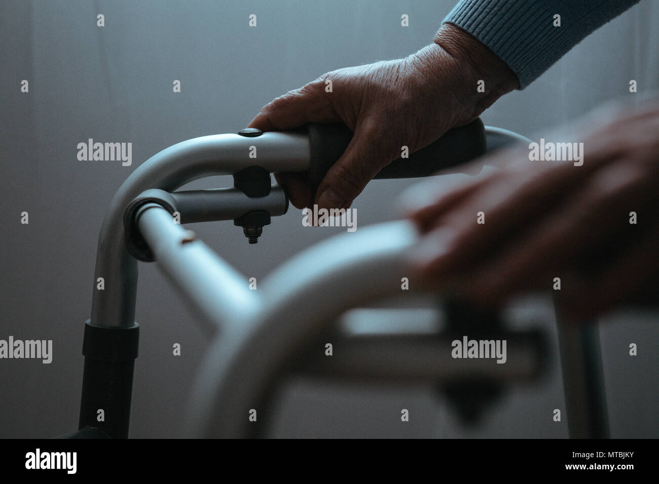 Disabled person holding hands on walker, close up - Stock Image