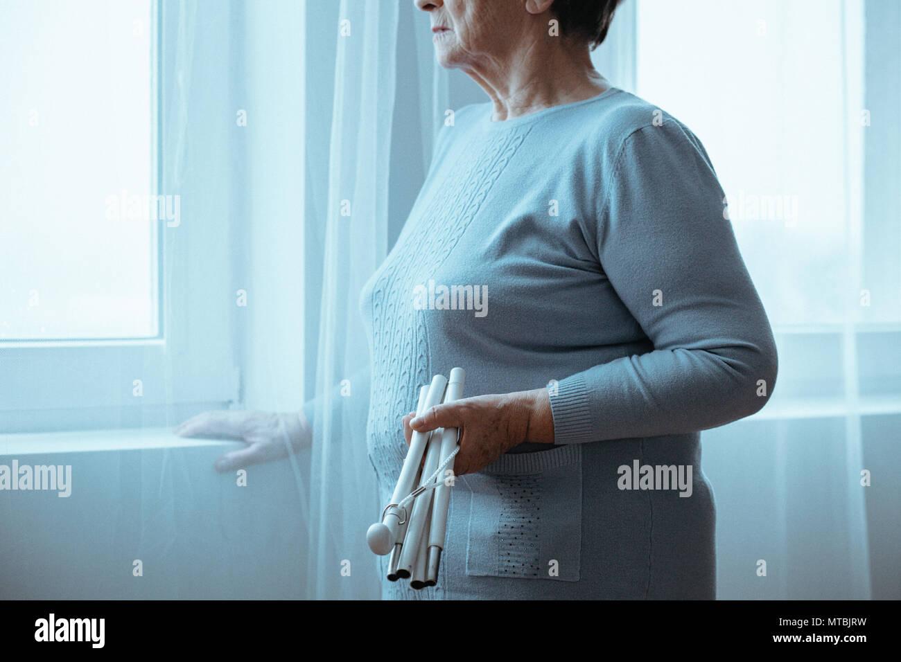 Senior, blind woman holding white cane, standing beside window - Stock Image