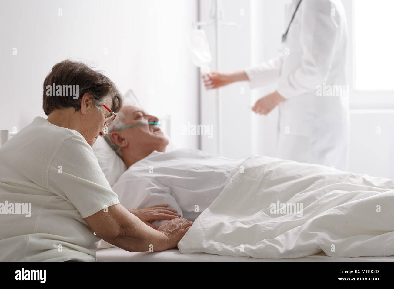 Senior woman with seriously ill husband in hospital Stock Photo