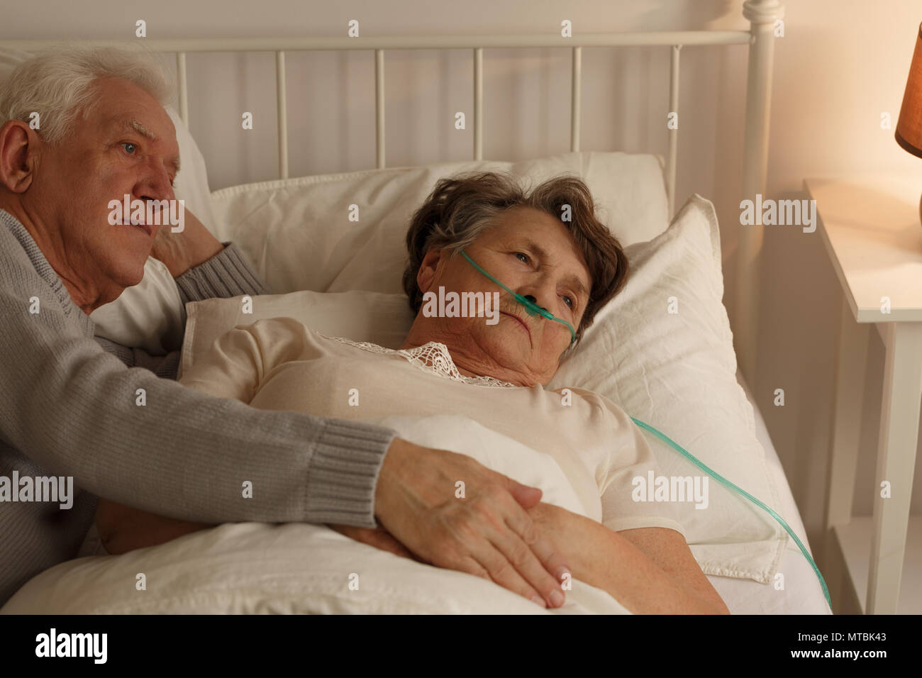 Man lying on bed next to elderly dying sick wife - Stock Image