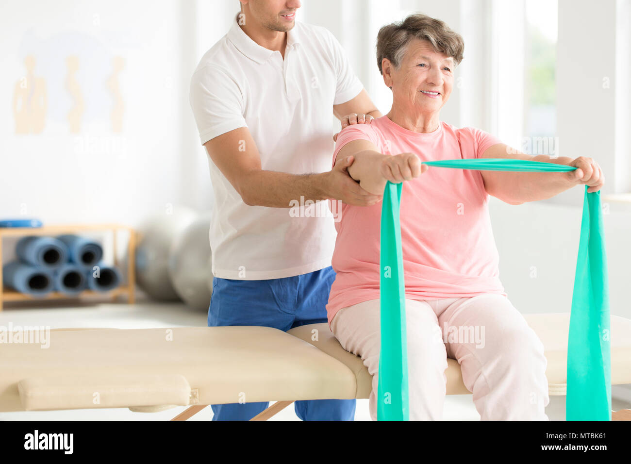 Elderly woman doing active pnf exercises with a teal scarf as a part of her rehabilitation program with a physiotherapist - Stock Image