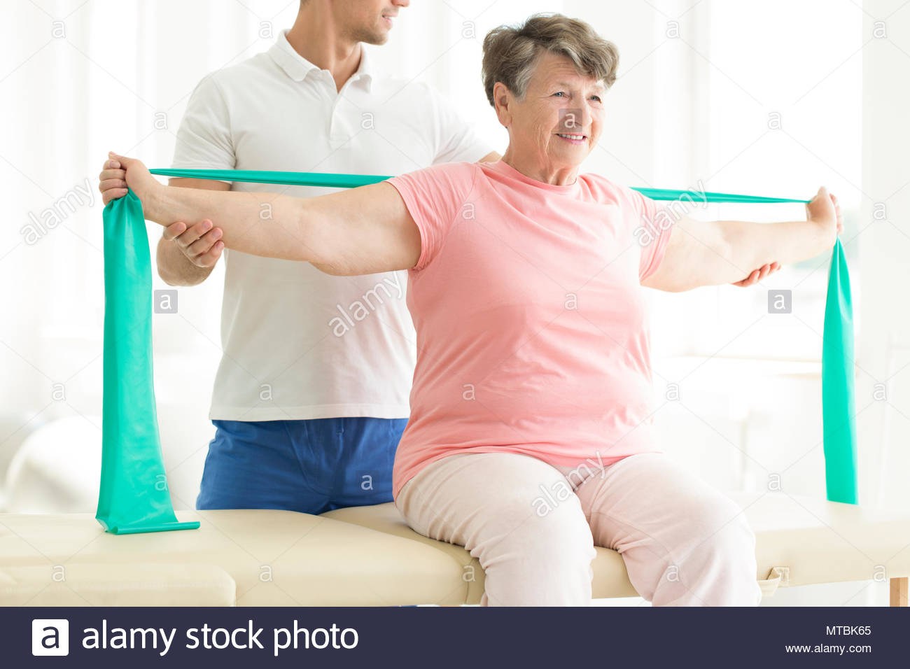 Physiotherapist providing help with easing the pain of joints through pnf exercises involving a scarf for his elderly patient - Stock Image