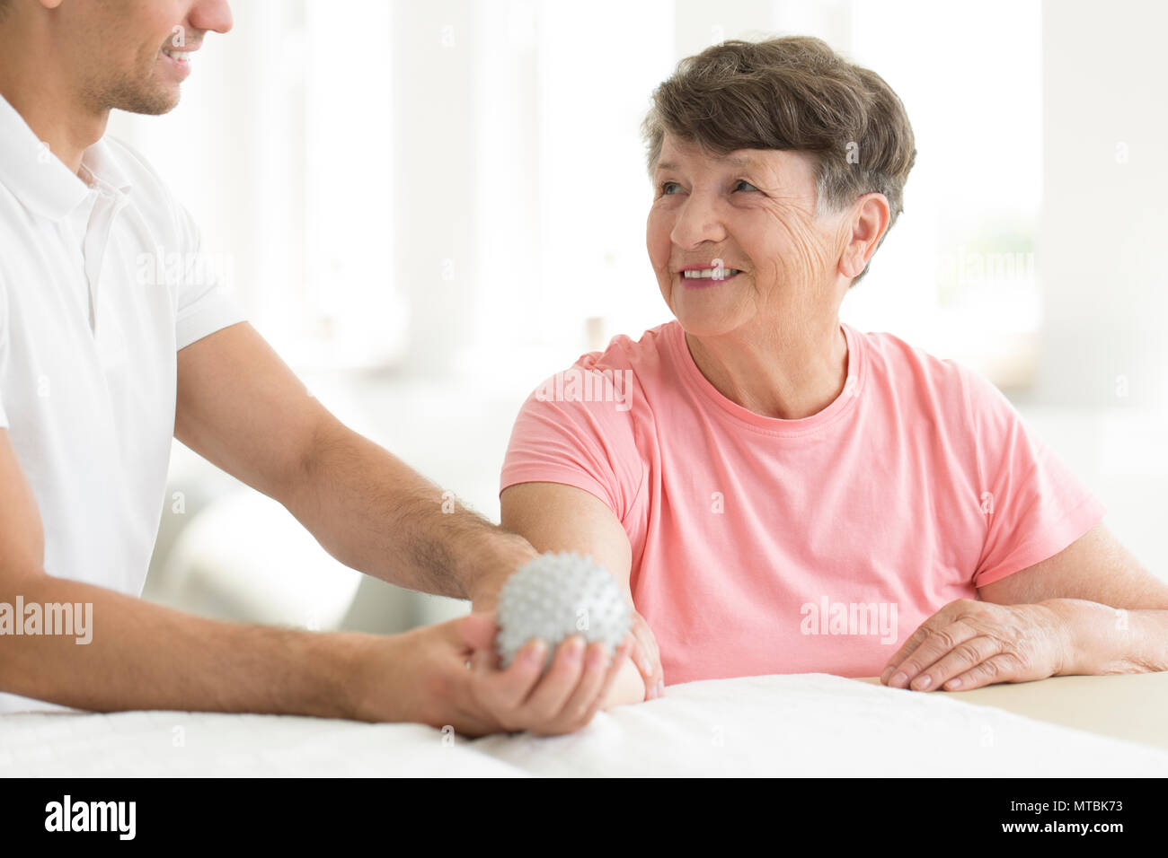 Hospital patient holding a grey, spiked rehabilitation ball in her right hand during physiotherapy - Stock Image