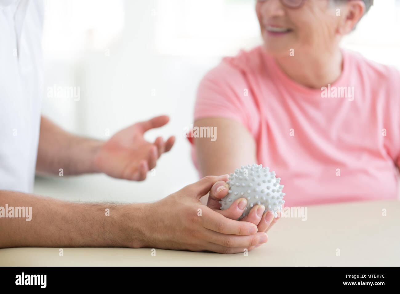 Nursing home patient doing active pnf exercises with a grey spiked ball used for rehabilitation purposes - Stock Image