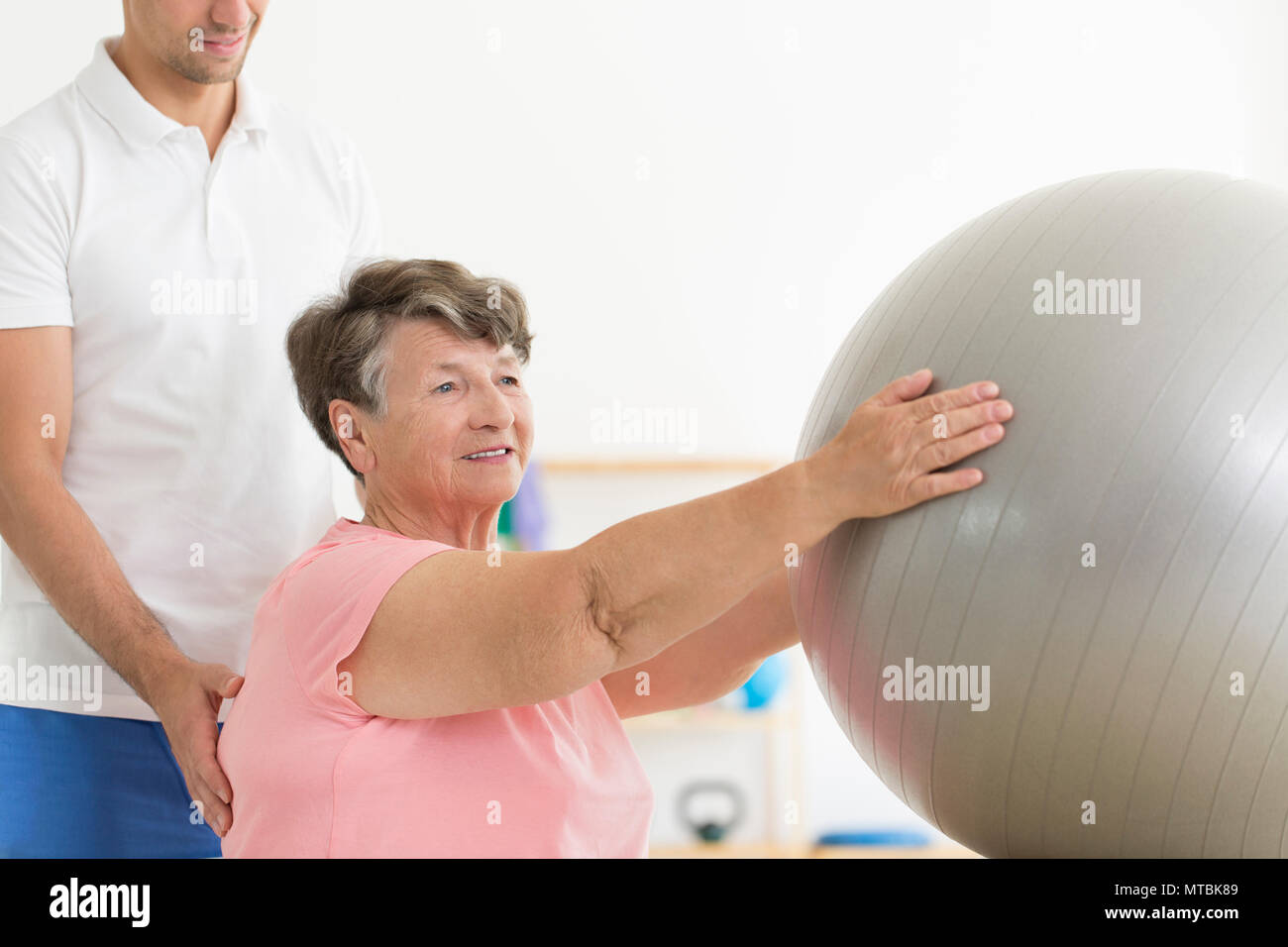 Elderly patient having an isometric physiotherapy session with a grey fit ball and a physical therapist - Stock Image