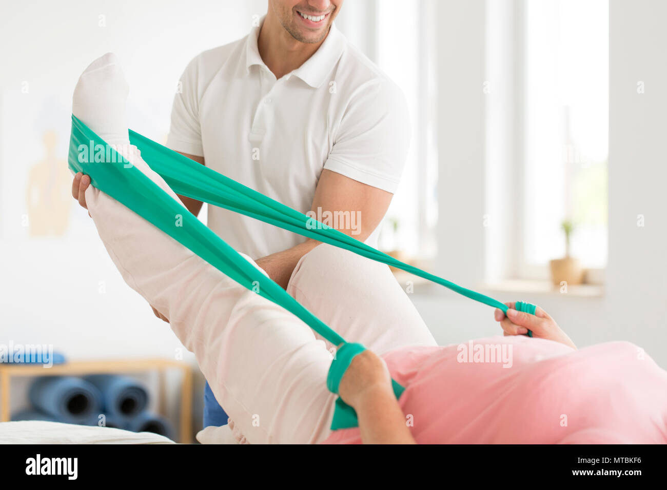 Professional physiotherapist performing isometric pnf exercises with his elderly patient in a private office using a teal scarf - Stock Image