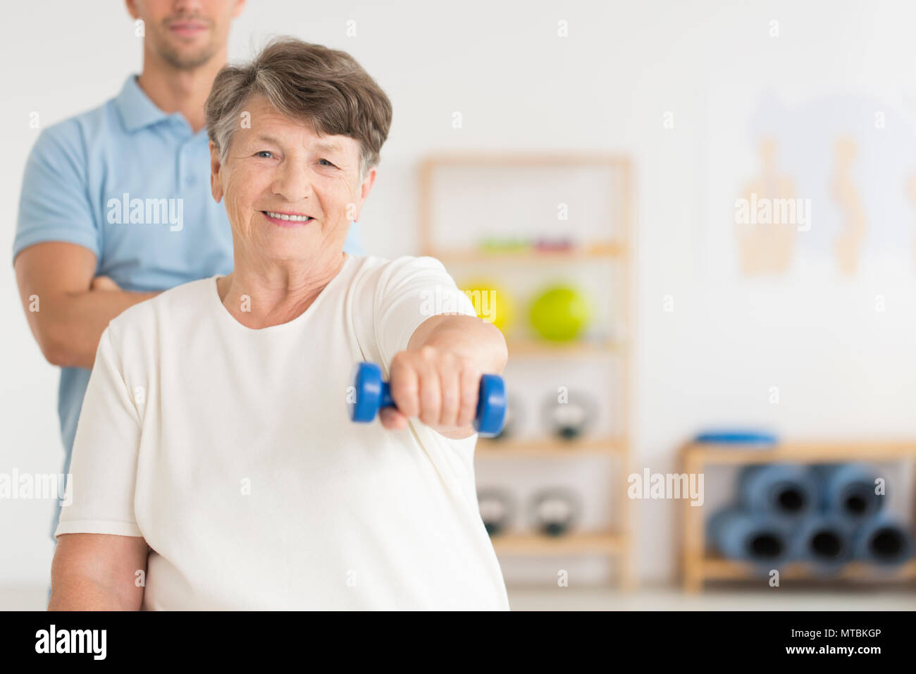 Elderly woman doing active, isometric exercises guided by physical therapist at the hospital rehabilitation center - Stock Image