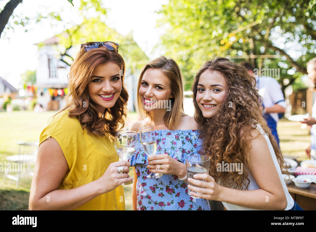 Portrait of three women on a family celebration or a barbecue party outside in the backyard. - Stock Image