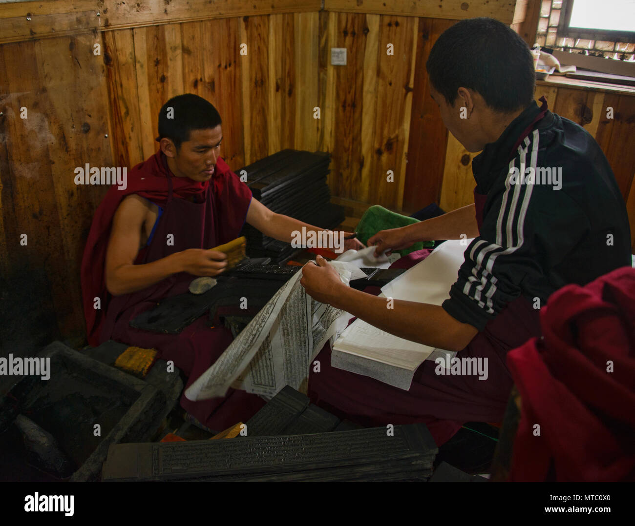 Monks at the Barkang printing press at Labrang Monastery, Xiahe, Gansu, China - Stock Image