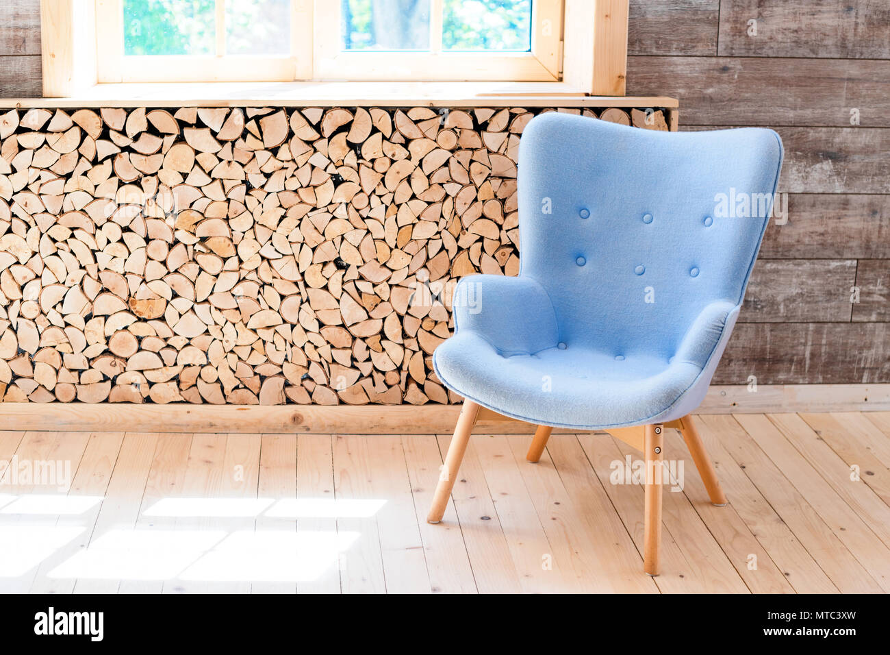 Comfortable soft armchair in scandinavian eco loft apartment. Modern minimalist living room with woodpile - Stock Image