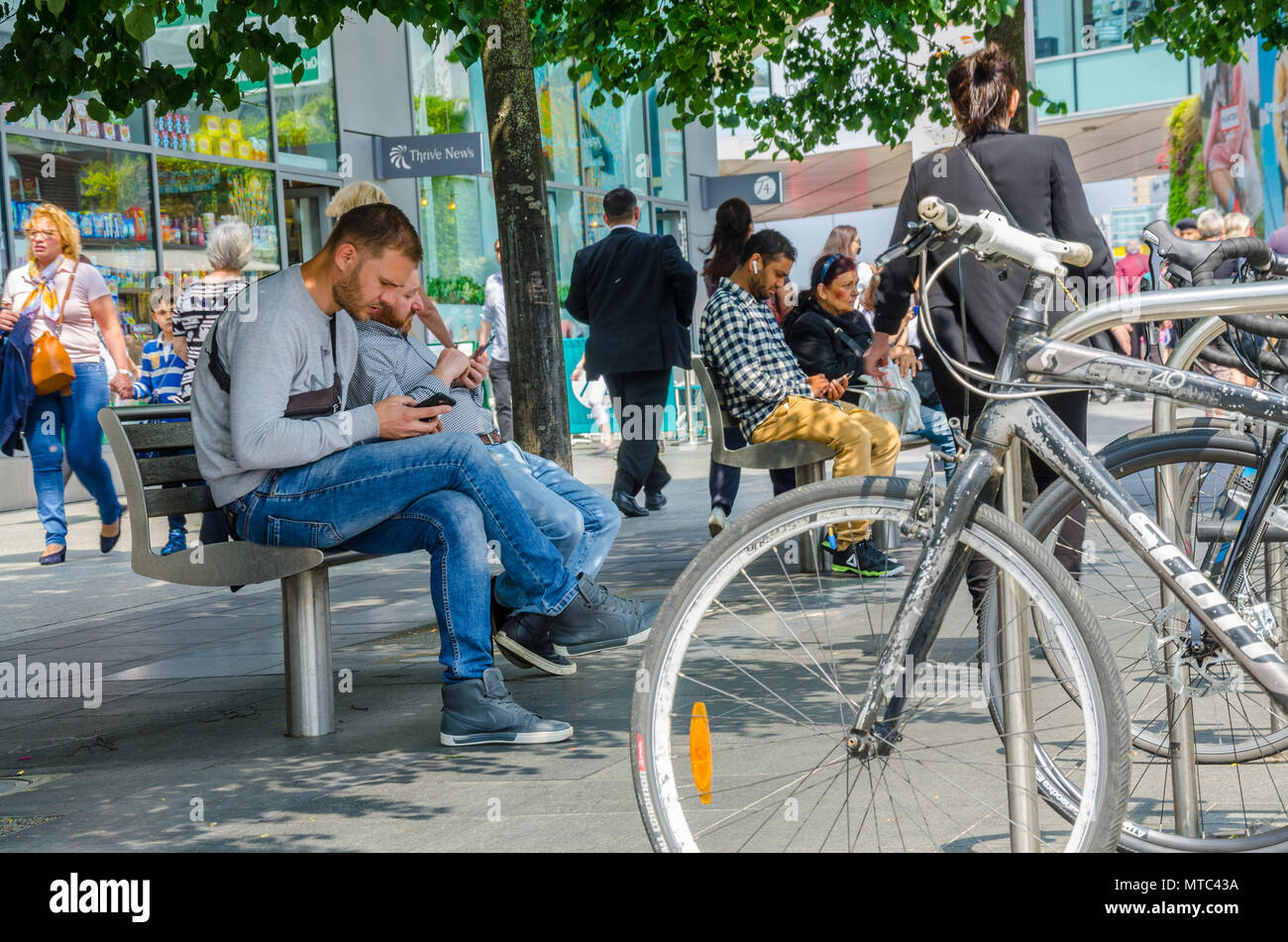 Bicycles parked in a bicycle rack next to benches with people sat preoccupied with their mobile phones, - Stock Image