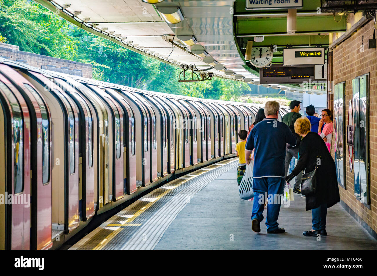 A train waits int he station as passengers walk down the platform at White City London Underground Station. - Stock Image