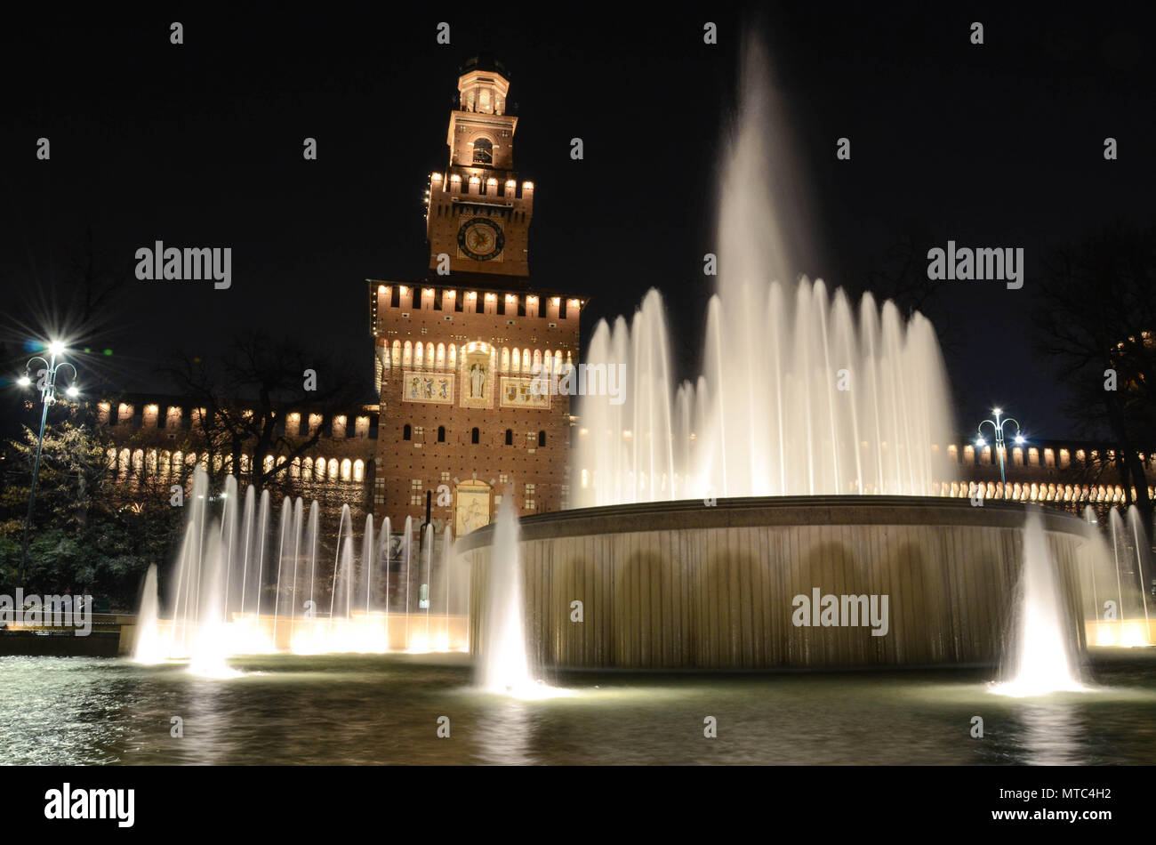 Water fountain in front of the Sforza Castle (Castello Sforzesco) at night, Milan, Lombardy, Italy, January 2018 - Stock Image