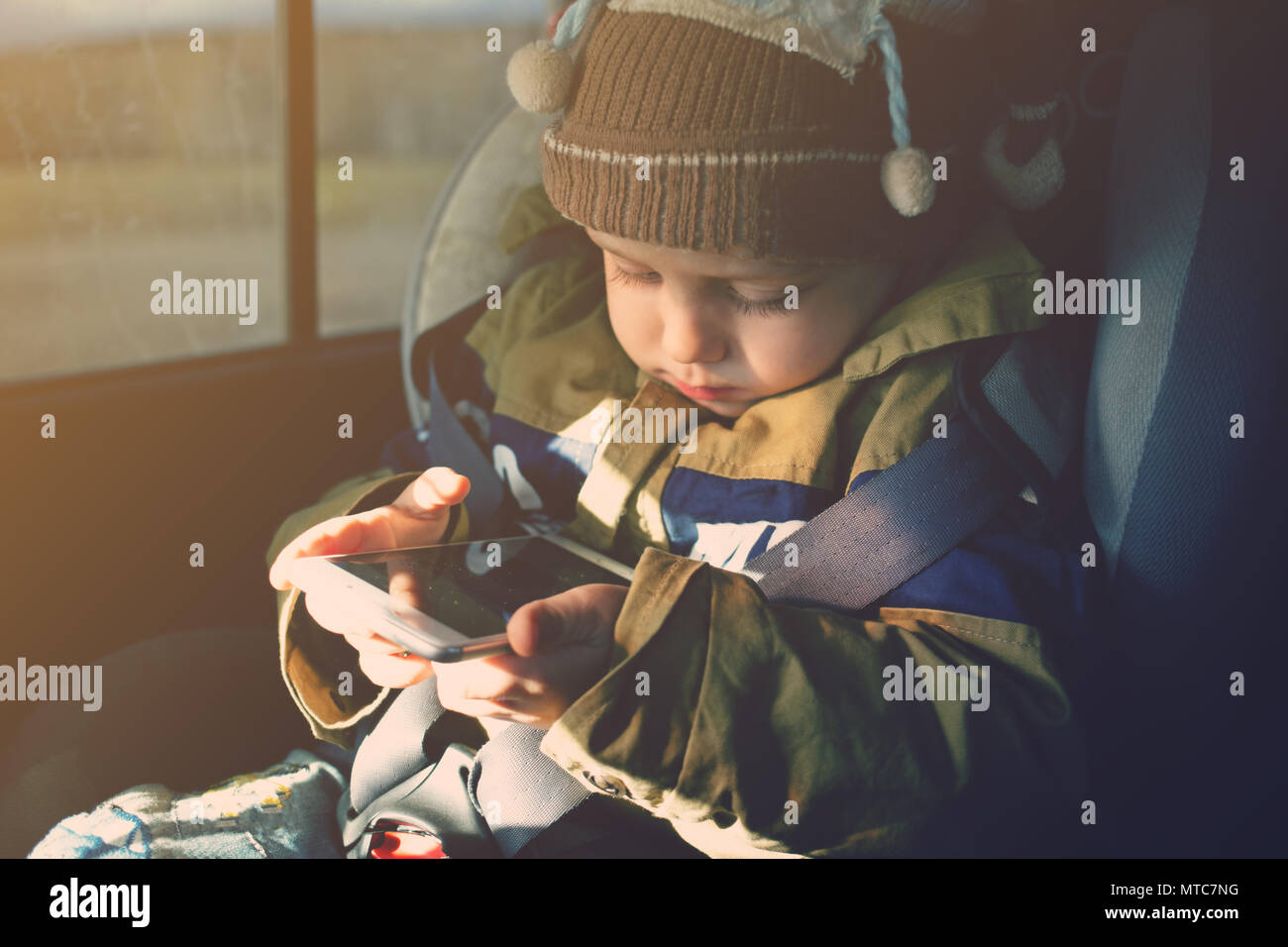 baby boy using phone in the car Stock Photo