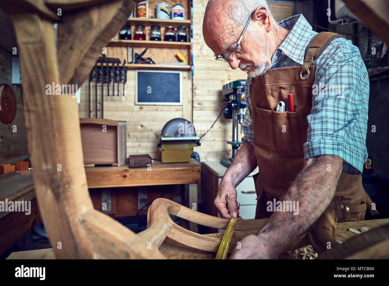 senior carpenter on duty in his workshop - Stock Image