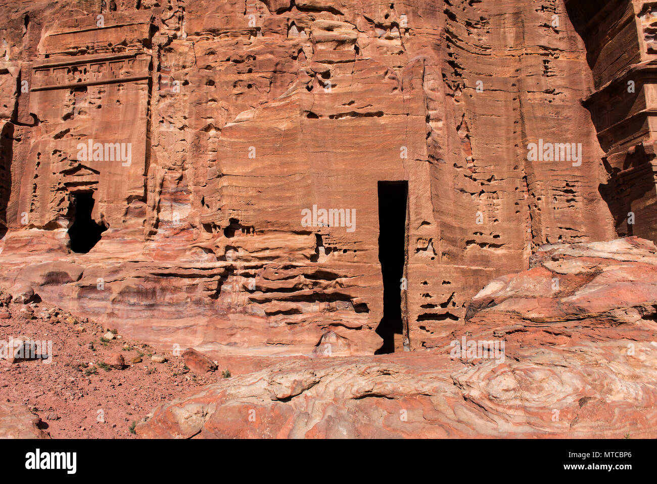 Entrance of a cave, royal tomb in Petra, Jordan. Underground ancient rock carving, used as burial place - Stock Image