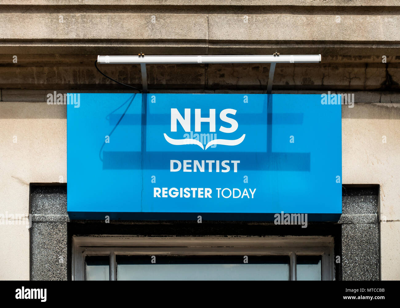 Sign outside the surgery of an NHS dentist, encouraging potential patients to 'register today'. - Stock Image