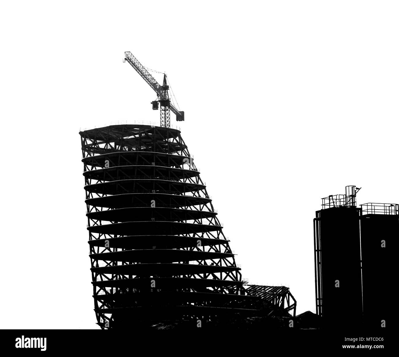 Construction site with crane and scaffolding seen as a silhouette - Stock Image