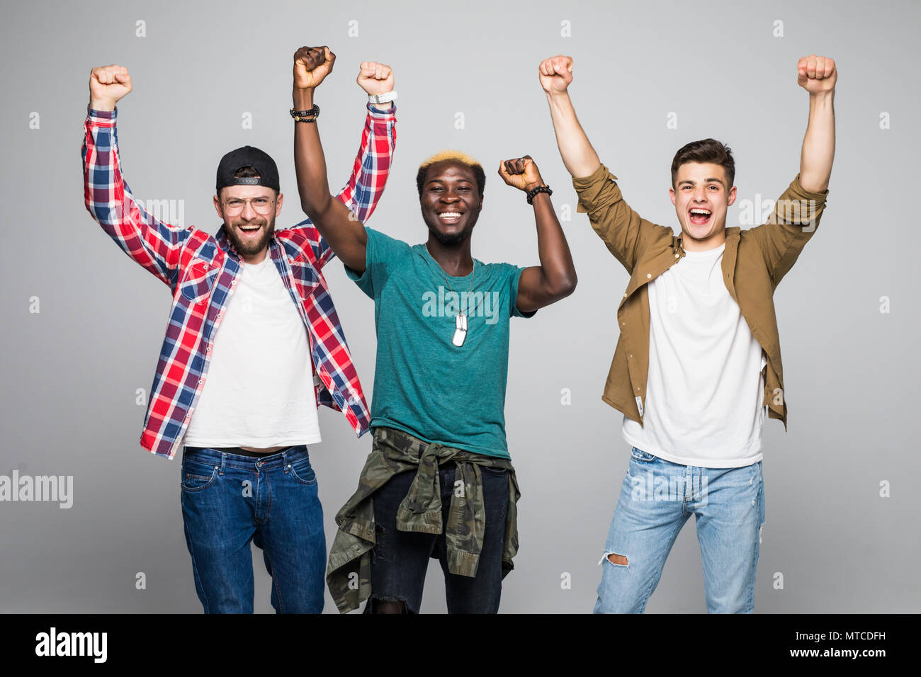 Three young cheery men football fans celebrating isolated over yellow background - Stock Image