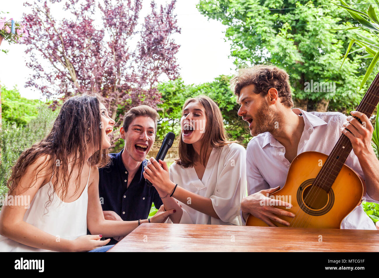 group of young friends having fun singing a song in the