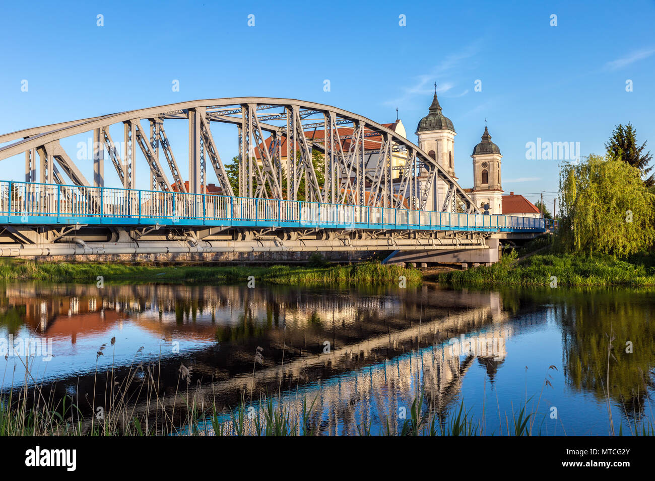View at bridge over the Narew river and baroque Church of the Holy Trinity in Tykocin town, Podlasie, Poland. Stock Photo