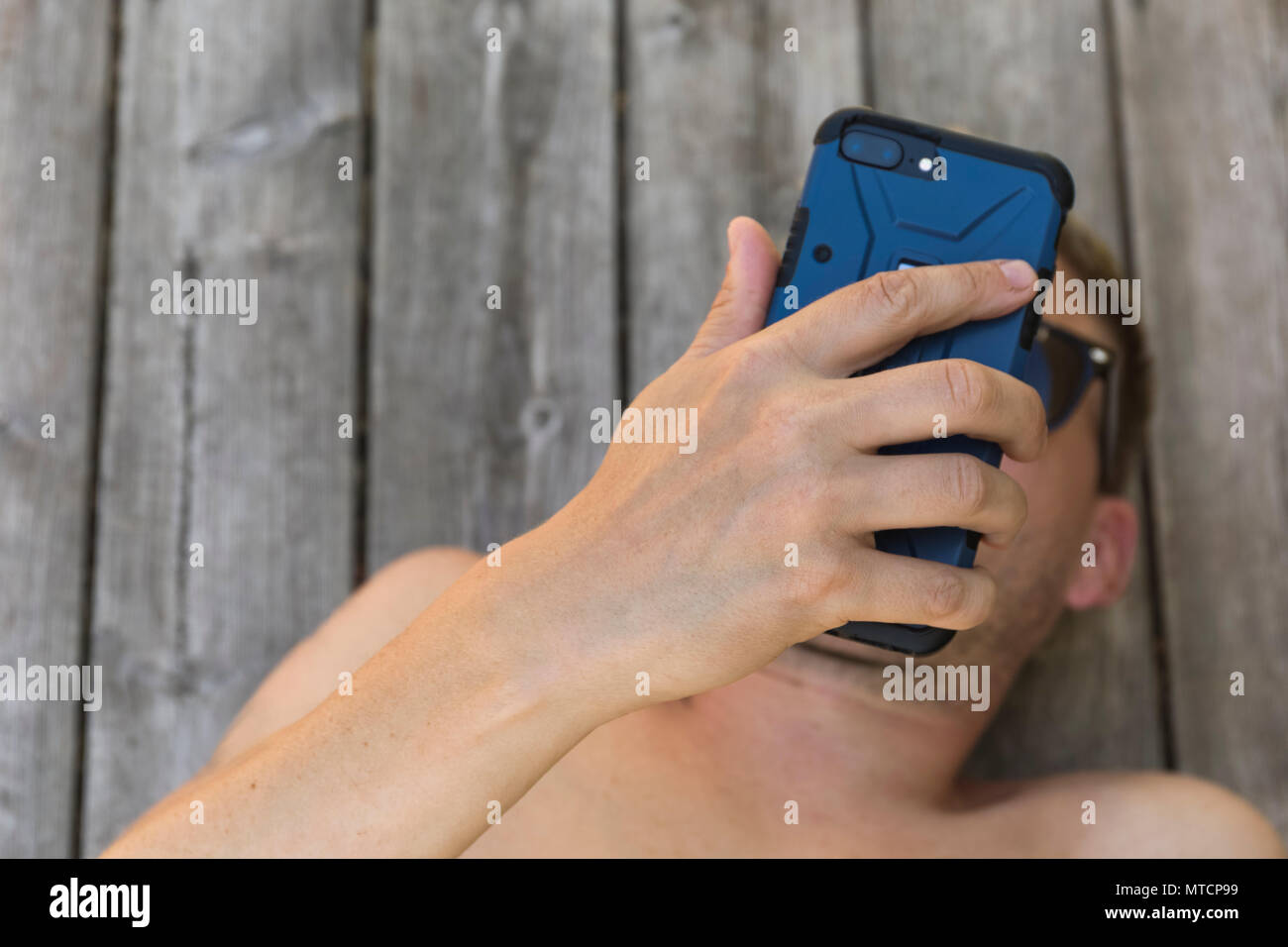Barechested mid adult 40s caucasian man using smartphone mobile phone outdoors on patio when relaxing in sun - Stock Image