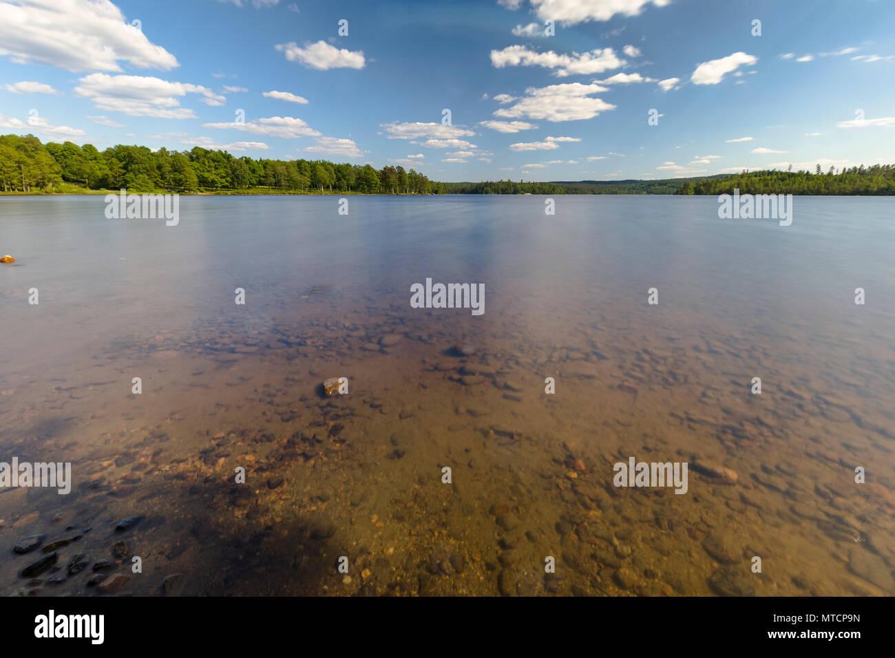 Beautiful long exposure daytime view of Lake Uspen in Lerum municipality, Sweden, on beautiful hot weather day - Stock Image