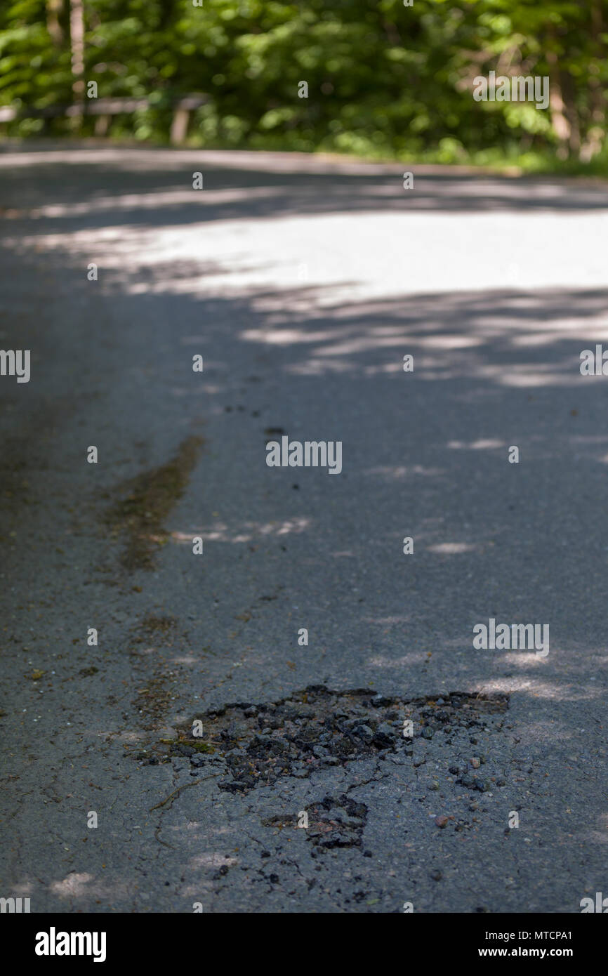 Close up view of beginning pothole on cracked asphalt road surface going into a corner - Stock Image