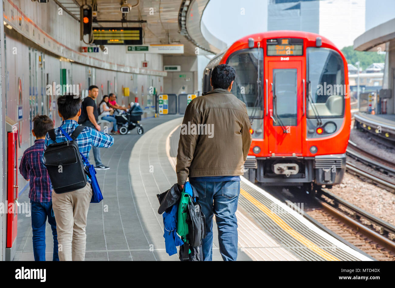 A family walk down the platform towards a waiting train at Wood Lane London Underground Station. - Stock Image