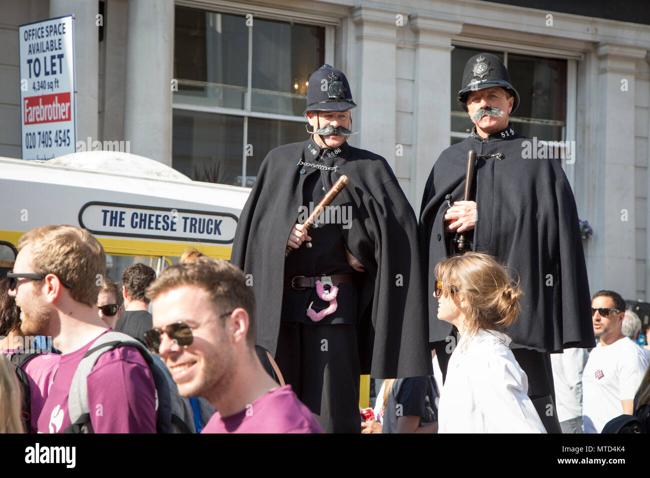 Street entertainers on stilts in Victorian police uniform at the start of London Legal Walk 2018 - Stock Image