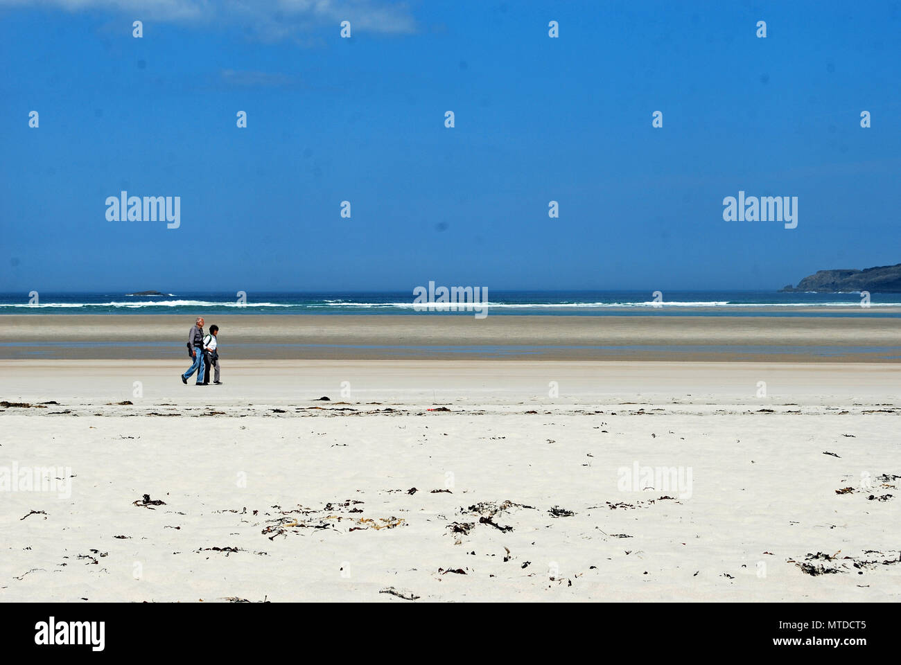 Ardara, County Donegal, Ireland. 29th May 2018 A tourist couple walk on Maghera beach, Ardara, on the hottest day in Ireland so far this year. Credit: Peter Alexander/Alamy Live News - Stock Image