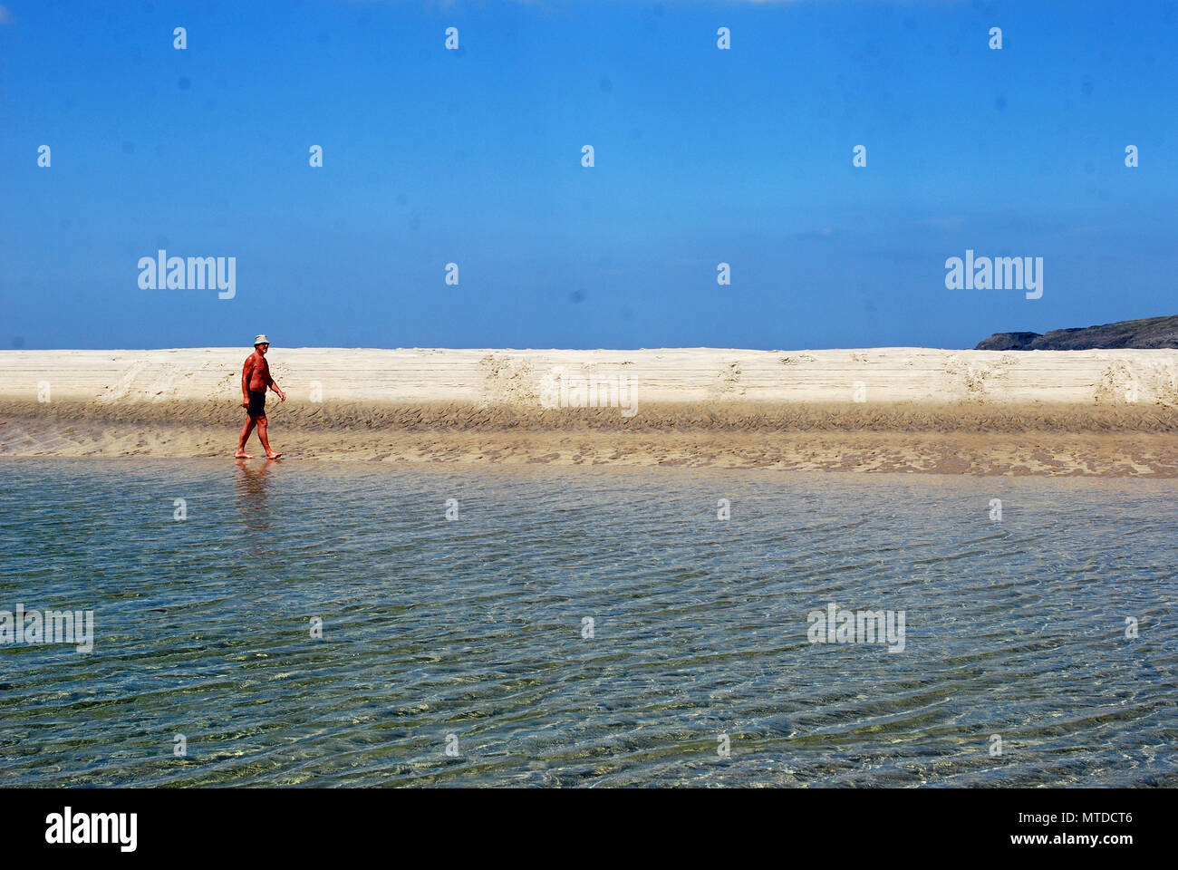 A sunbather strolls across Maghera Beach on the hottest day in Ireland so far this year. - Stock Image
