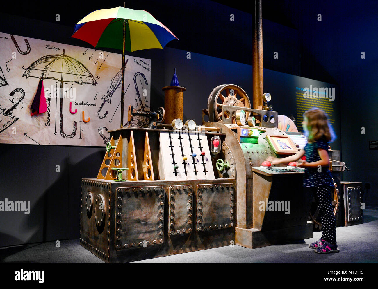 """30 May 2018, Germany, Speyer: Ida stands beside a replica of the umbrella machine from the film """"Sams im Glueck"""" (lit. """"Sams in luck"""") at the exhibition """"Das Sams und die Helden der Kinderbuecher"""" (lit. """"Sams and the heroes of childrens' books"""") at the Historical Museum of Rhineland-Palatinate. The exhibition is running from 01 June 2018 to 06 January 2019. Photo: Uwe Anspach/dpa Stock Photo"""