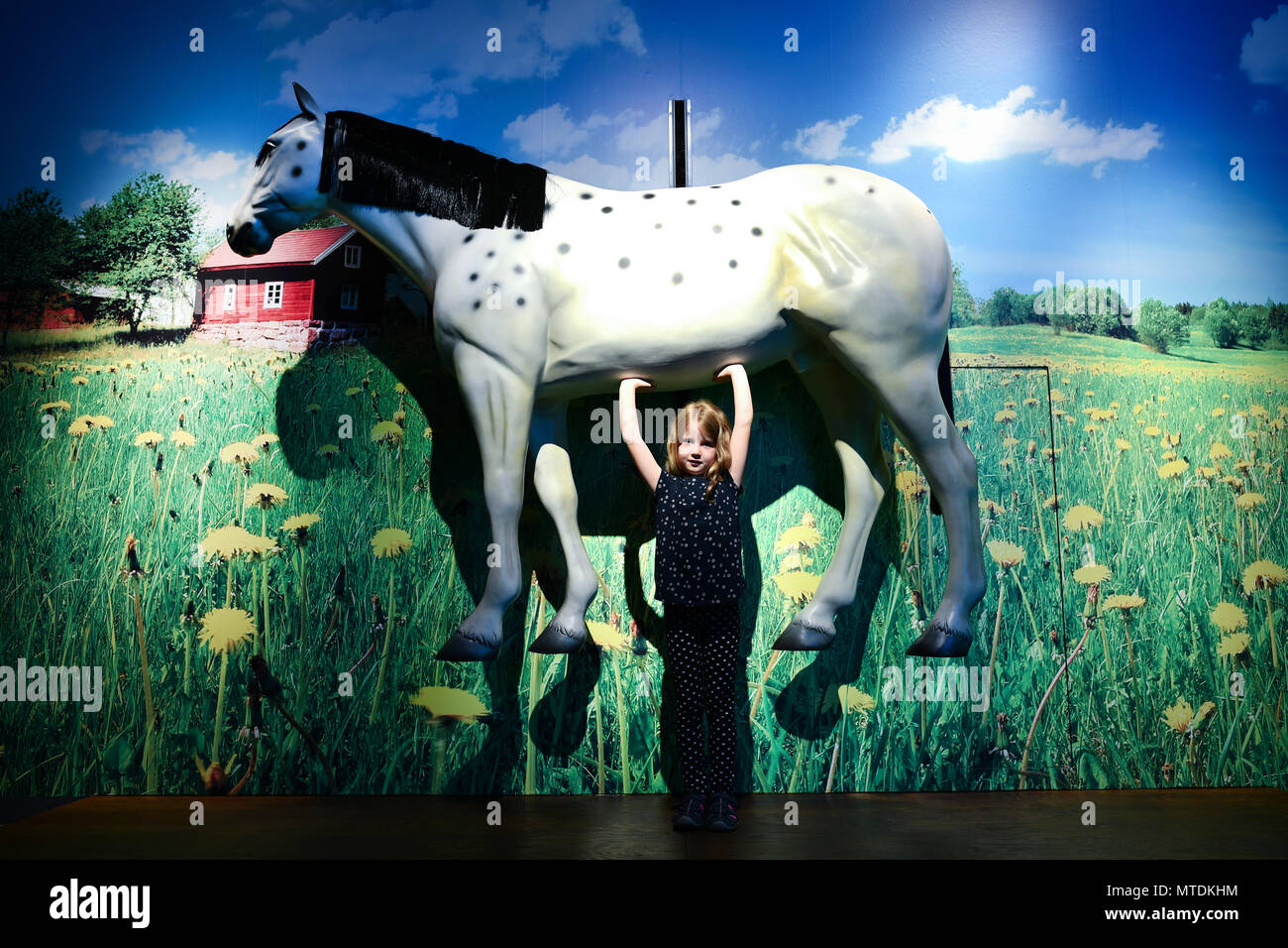 """dpatop - 30 May 2018, Germany, Speyer: Ida holds up a replica of a horse in the area dedicated to Astrid Lindgren's creation Pippi Longstocking at the exhibition """"Das Sams und die Helden der Kinderbuecher"""" (lit. """"Sams and the heroes of childrens' books"""") at the Historical Museum of Rhineland-Palatinate. The exhibition is running from 01 June 2018 to 06 January 2019. Photo: Uwe Anspach/dpa Stock Photo"""