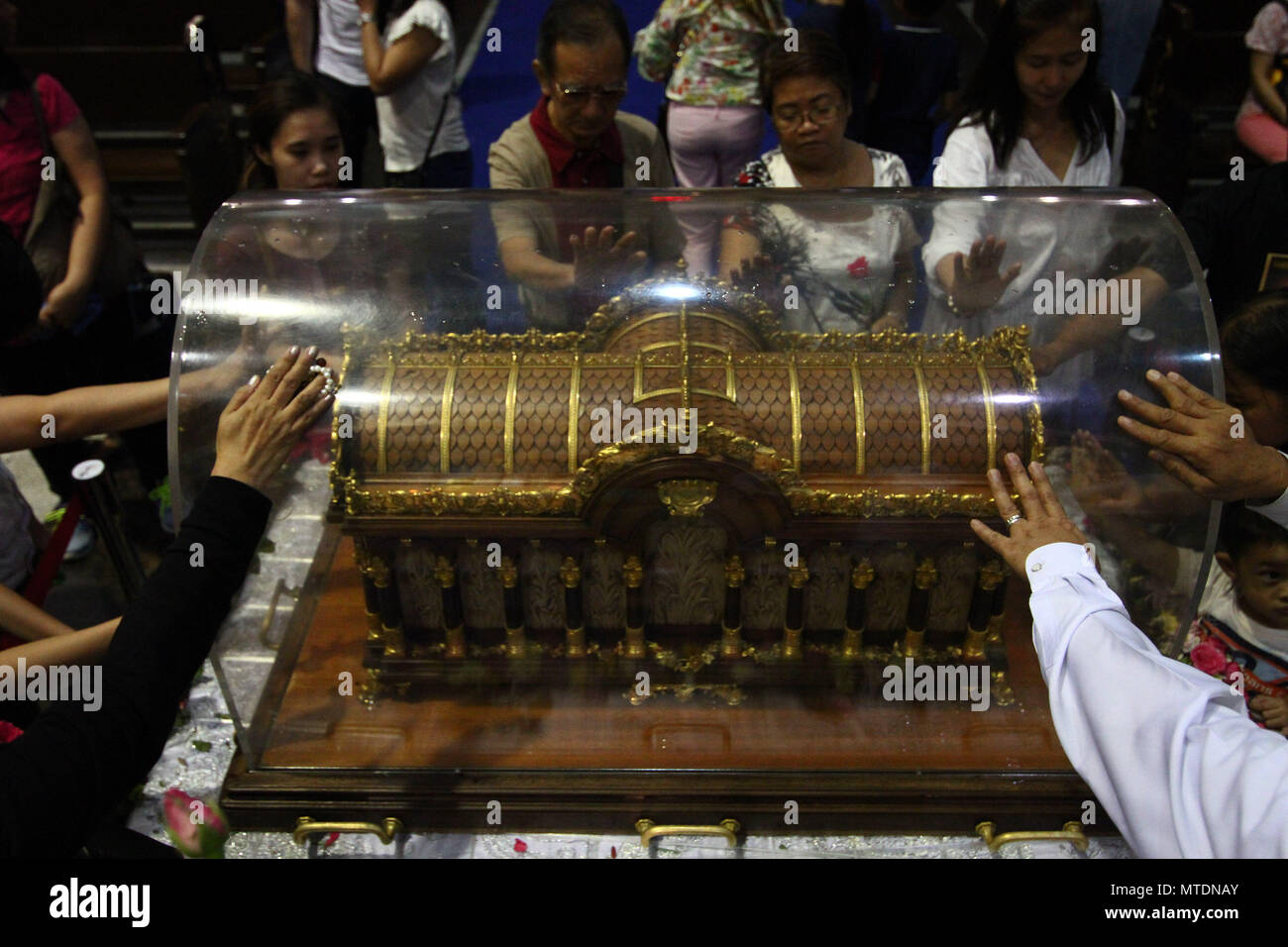 Catholic devotees seen touching the Shrine of Saint Therese of the Child Jesus in New Port City in Pasay, Metro Manila, for the veneration of  the holy relic of Saint Therese of Lisieux. The reliquary containing the bones of Saint Therese has been on a nation wide tour and is on its last few days in Manila before heading back to France. - Stock Image