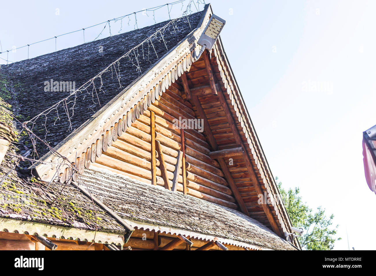 A gable wooden roof. Wooden decoration. The roof is covered with wooden shingles. The pediment is made of logs. - Stock Image