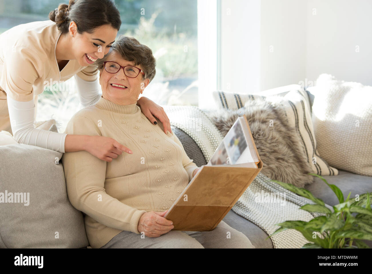 Grandmother sitting on a couch in a sunny room, looking at a photo album and sharing fond memories with a tender caregiver - Stock Image