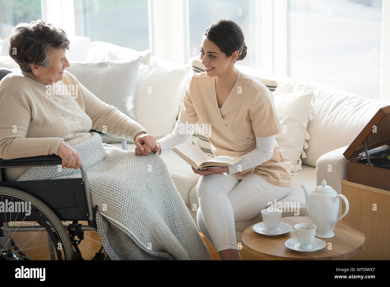 A disabled old woman in a wheelchair holding the hand of a tender professional medical assistant during tea time in a living room of luxury retirement - Stock Image