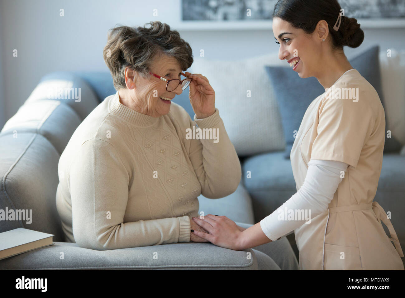 A tender caregiver kneeling down and facing a smiling older woman who is sitting on a sofa and holding her glasses - Stock Image