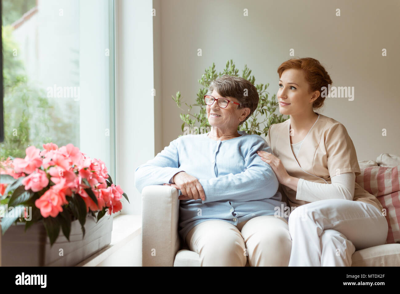 Geriatric woman and her professional caretaker sitting on a couch and looking through a window in a living room. Blooming flowers on a windowsill. - Stock Image