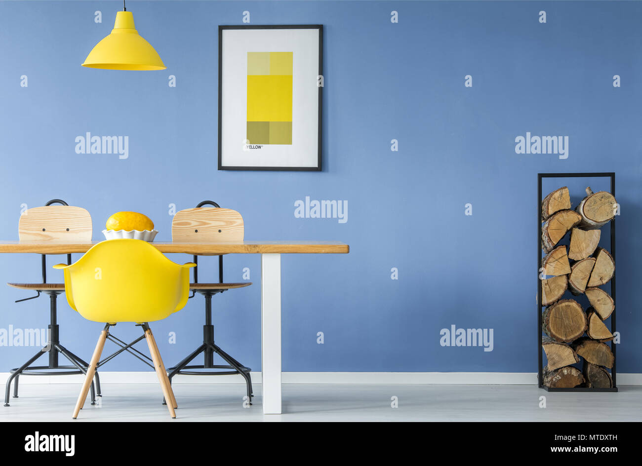 A yellow chair and a hanging lamp in an open space, minimal style interior with a melon in a dish on a table with a pile of firewood against a blue wa - Stock Image