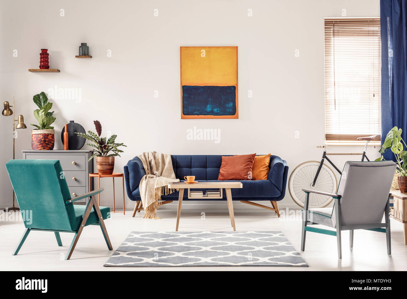 Real photo of a navy blue sofa with orange cushions and an ...