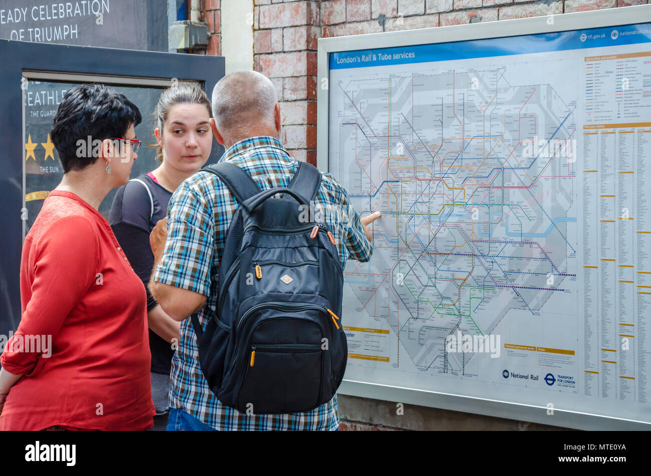 A family consult a map of The London underground at Hammersmith tube station to help navigate to their destination. - Stock Image