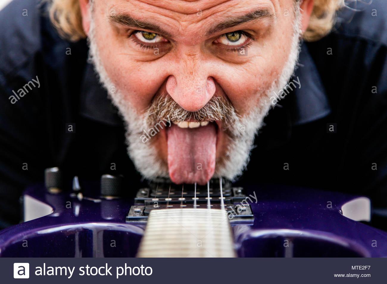 Man kisses his electric guitar - Stock Image